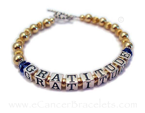 LLL-MB-08-Gold  This is a sterling silver and gold Gratitude bracelet. You pick the message, size, clasp and charms...  If you would like to put Swarovski crystals before and after the word(s) you choose enter it like this... GRATITUDE/dark blue